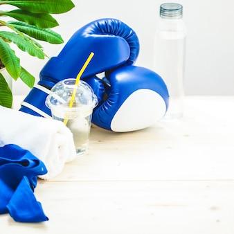 Conjunto para esportes, toalha, luvas de boxe e uma garrafa de água em um estilo de vida leve e saudável.