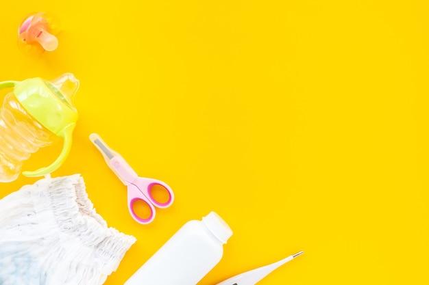 Conjunto para higiene infantil em um fundo amarelo, vista superior, plano leigo, copie o espaço.