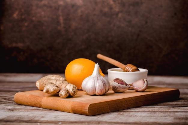 Conjunto para imunidade, vitamina c-mel, raiz de gengibre, limão, alho, em uma placa de madeira, fundo marrom