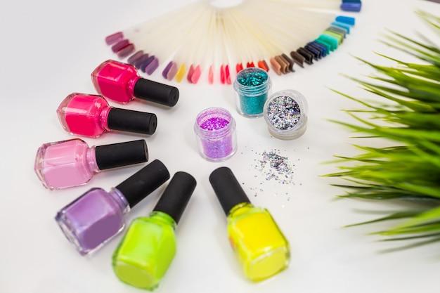 Conjunto para o design de manicure: muitos esmaltes coloridos e brilhos / brilhos em close-up da mesa branca.