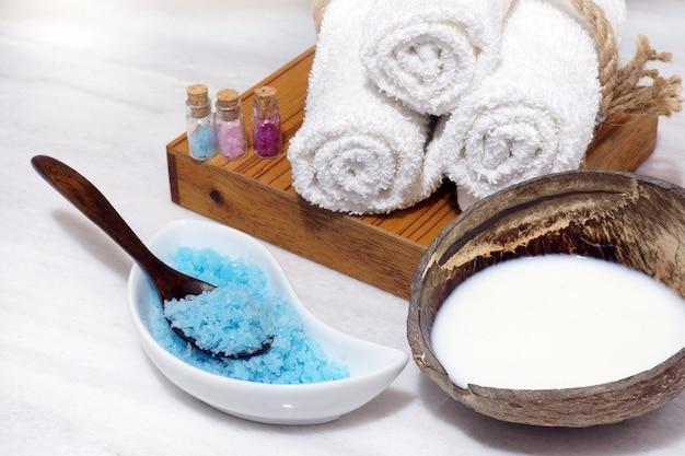 Conjunto para procedimentos de spa com óleo de coco, toalhas macias e sal de banho azul em uma mesa de mármore branco.