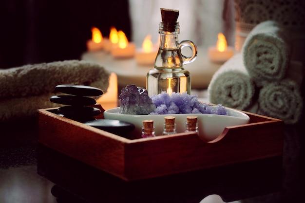 Conjunto para procedimentos de spa de pedras para massagem, óleo, sal marinho de violeta encontra-se em uma caixa de madeira. toalhas úmidas repousam sobre uma mesa de granito preto natural. velas elétricas queimam.