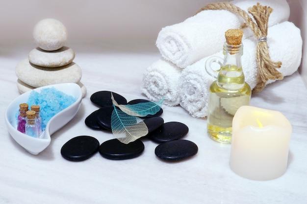 Conjunto para procedimentos de spa em uma mesa de mármore branco - óleo aromático, pedras para massagem quente, sal de banho azul e toalhas, amarradas com barbante.