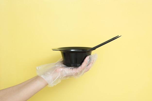Conjunto para tingimento de cabelo em casa ou salão de beleza na mão de uma mulher com pincéis de luva e tigela para tintura de cabelo
