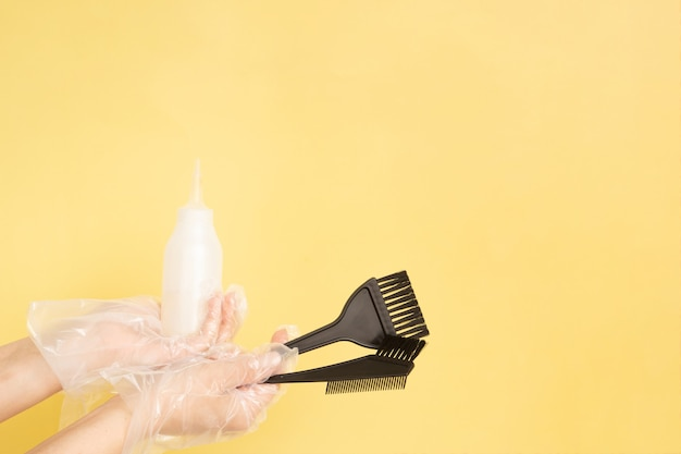 Conjunto para tingimento de cabelo em casa ou salão de beleza nas mãos de uma mulher com luvas - pincéis e garrafa em fundo amarelo