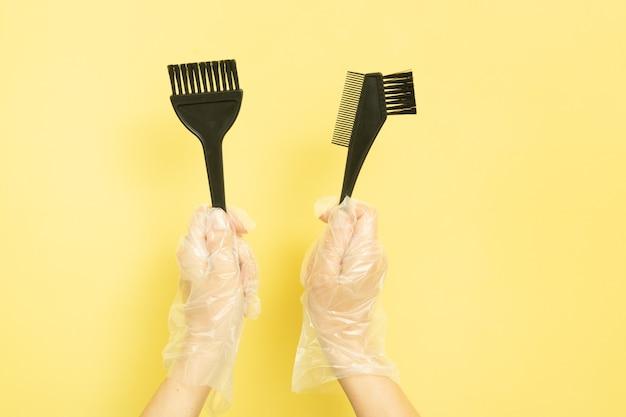 Conjunto para tingimento de cabelo em casa ou salão de beleza nas mãos de uma mulher com luvas. pincéis e tigela para tintura de cabelo em fundo amarelo