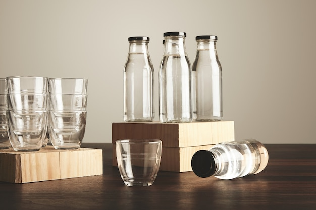 Conjunto perfeito de água pura, limpa e saudável em garrafas de vidro transparente e copos apresentados em madeira