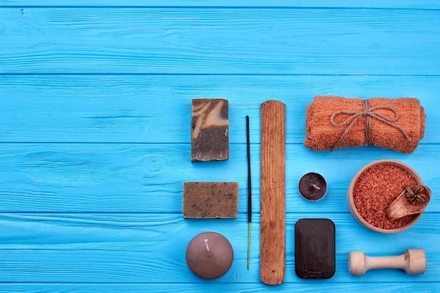 Conjunto plano leigos de coisas marrons na mesa de madeira azul. toalha enrolada com vela e sabonetes.