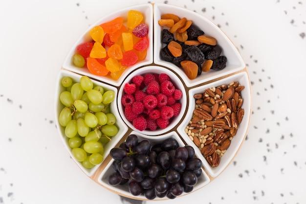 Conjunto redondo de pratos cheios de nozes, framboesas, doces, uvas e frutas secas no fundo branco