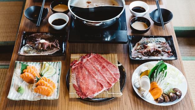 Conjunto shabu incluindo fatias raras de carne wagyu a5, shoyu shabu e base clara