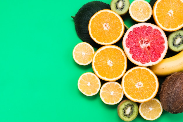 Conjunto tropical de frutas coloridas frescas sobre fundo verde