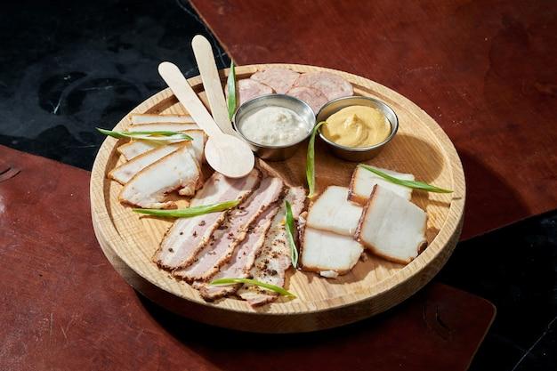 Conjunto ucraniano de diferentes tipos de bacon com mostarda e cebola numa superfície de madeira. banha ou salo