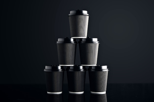 Conjunto vazio de copos de papelão preto para retirar, fechados com tampas em forma de pirâmide apresentadas em preto e espelhadas. apresentação de varejo