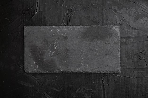Conjunto vazio de tábua de corte de pedra com espaço de cópia para texto ou comida com espaço de cópia para texto ou comida, vista de cima plana lay, em fundo preto de mesa de pedra escura