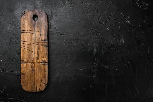 Conjunto vazio de tábua de madeira, vista superior plana, com espaço de cópia para o texto ou seu produto, sobre fundo preto de mesa de pedra escura