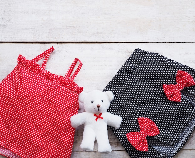Conjunto vestido de verão da menina crianças e boneca de pelúcia em fundo de madeira