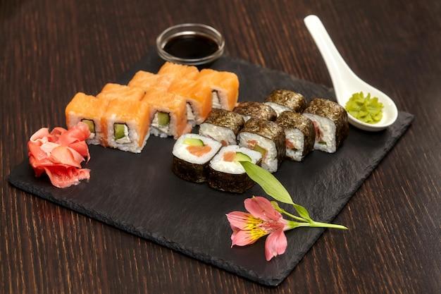 Conjuntos de sushi rolos na placa de ardósia preta