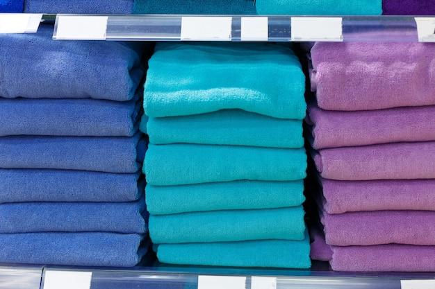 Conjuntos de toalhas multicoloridas em uma prateleira de uma loja