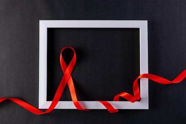 Conscientização contra a aids com fita vermelha embrulhada em molduras de fotos brancas em preto