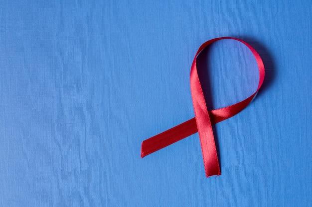 Conscientização do câncer de mama fita vermelha em fundo azul