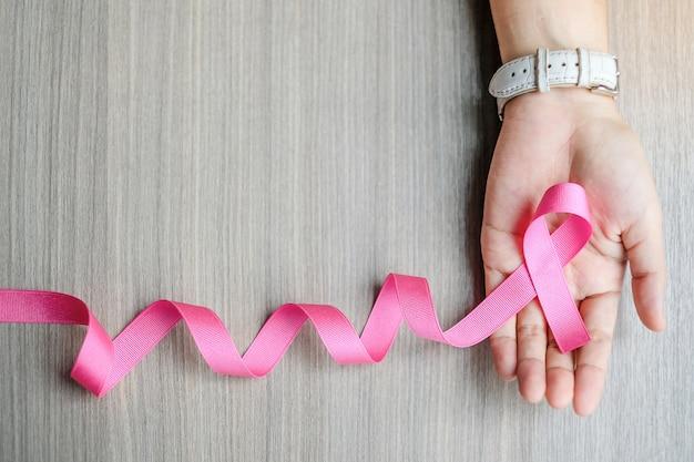 Conscientização do câncer de mama, mão de uma mulher segurando a fita rosa