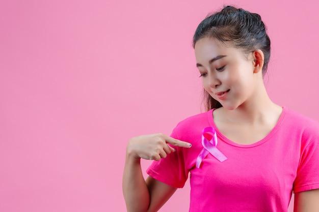 Conscientização do câncer de mama, mulher de camiseta rosa com fita de cetim rosa no peito, apoiando o símbolo