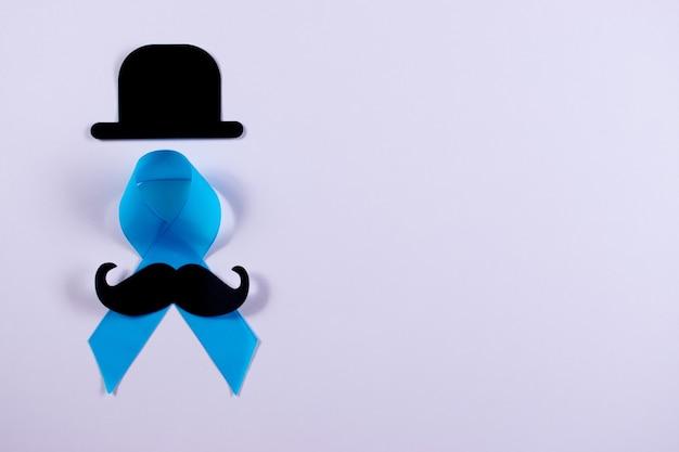 Conscientização do câncer de próstata, luz - fita azul com bigode e chapéu em fundo branco, com espaço de cópia.