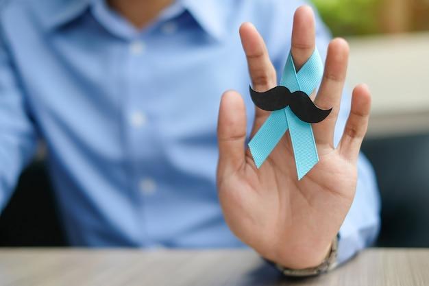 Conscientização do câncer de próstata, mão de homem segurando a luz da fita azul
