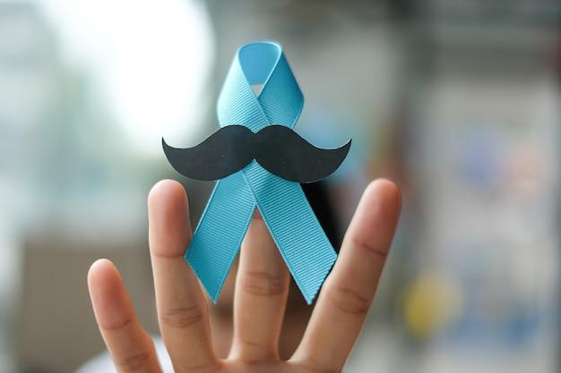 Conscientização do câncer de próstata, mão de uma mulher segurando a fita azul clara
