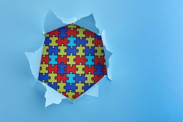 Conscientização mundial do autismo, conceito com padrão de quebra-cabeça ou quebra-cabeça em orifício de corte de papel