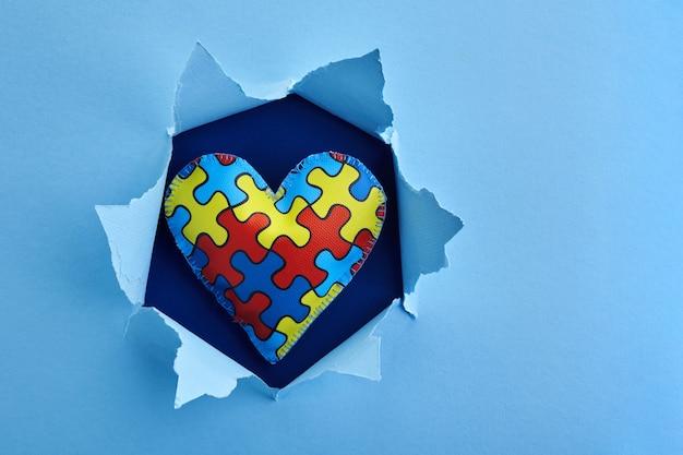 Conscientização mundial do autismo, conceito com padrão de quebra-cabeça ou quebra-cabeça no coração em um buraco de papel