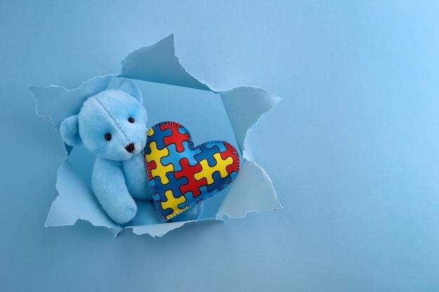 Conscientização mundial do autismo, conceito com ursinho de pelúcia segurando um quebra-cabeça ou um padrão de quebra-cabeça no coração em um buraco de papel