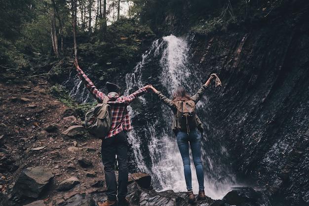 Conseguimos! retrovisor de corpo inteiro de um jovem casal levantando as mãos em pé perto da cachoeira