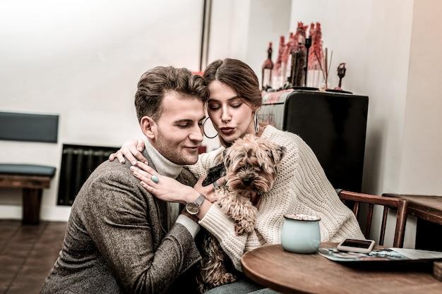 Conseguir um novo membro da família. um casal feliz está comprando um pequeno cachorro terrier engraçado