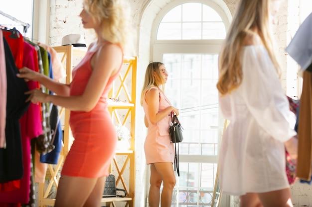 Conseguir um vestido novo. desgaste, loja de roupas durante as vendas, coleção de verão ou outono. mulheres jovens em busca de roupas novas. conceito de moda, estilo, ofertas, emoções, vendas, compras. novo shopping.