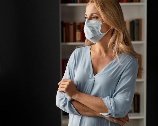 Conselheira de mulher preocupada em tiro médio com máscara facial no escritório