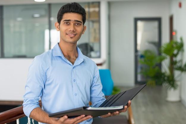 Conselheiro financeiro indiano positivo segurando a pasta aberta