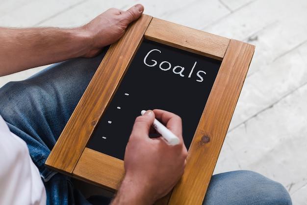 Conselho com novos objetivos. digite novos objetivos. a inscrição em giz em um quadro negro em uma moldura de madeira.