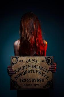 Conselho da ouija para adivinhação. menina, segurando, um, ouija, tábua