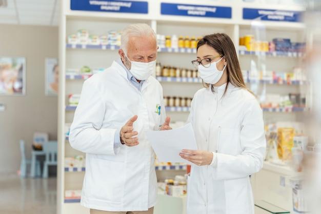 Conselho de colega. documentação e papelada em farmácias durante o vírus corona. um farmacêutico sênior explica a documentação na farmácia para um jovem farmacêutico. eles usam uniformes e máscaras