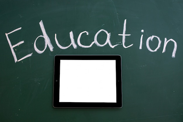 Conselho escolar com a inscrição educação e tablet ipad com tela em branco