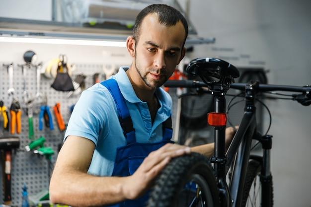 Conserto de bicicletas na oficina, homem verifica os pneus