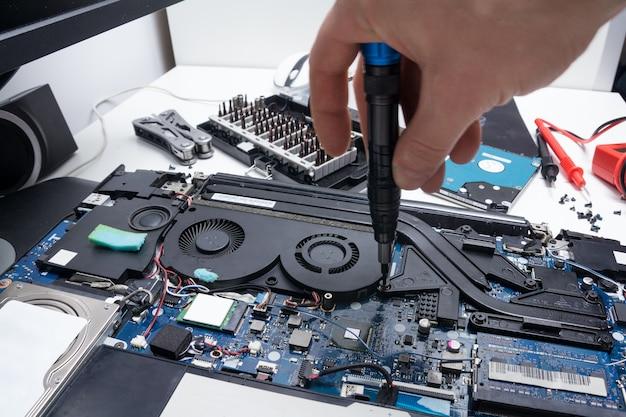 Conserto de laptop em uma oficina, mão masculina segura uma chave de fenda