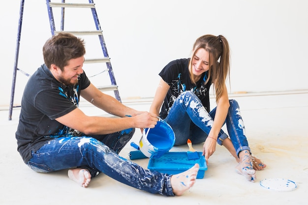 Conserto, reforma e conceito de pessoas - casal vai pintar a parede, está preparando a cor e os pincéis