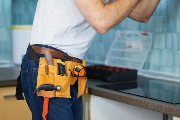 Consertos confiáveis tiraram fotos de um jovem trabalhador braçal usando um cinto de ferramentas consertando um exaustor de cozinha