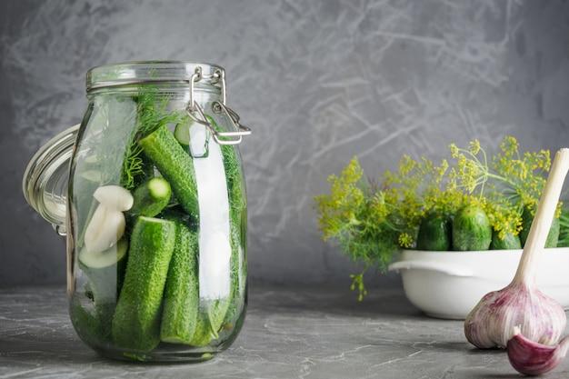 Conservação em vinagre e pepino da fermentação no frasco de vidro com aneto e alho no cinza. espaço para texto.