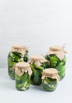 Conservação em vinagre e pepino da fermentação no frasco de vidro com aneto e alho no cinza.