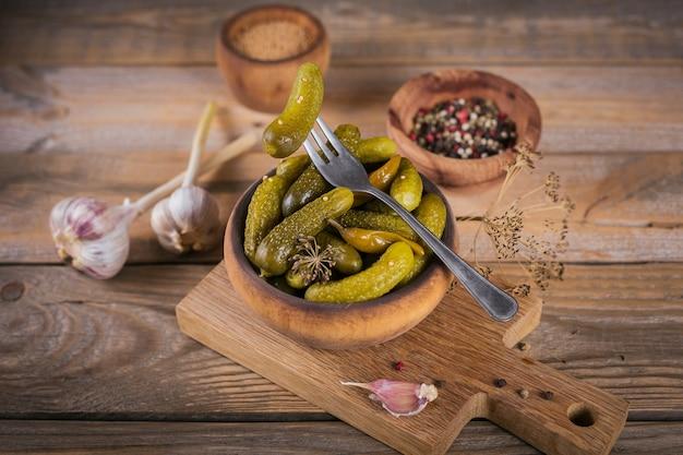Conservando temperos de pepino em conserva e alho na mesa de madeira