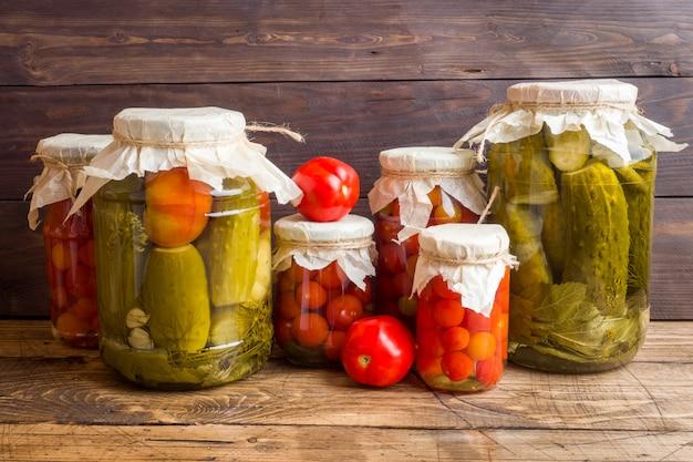 Conservas caseiras de legumes em latas. tomates em conserva e pepinos em estilo rural.