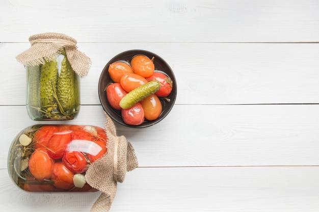 Conservas de legumes pepino e tomate em potes de vidro na placa de madeira ver os de cima preparações caseiras de outono colheita trabalhos de casa e tradições.